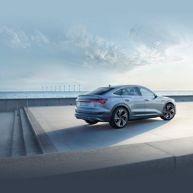 e-tron Sportback near sea with wind turbines